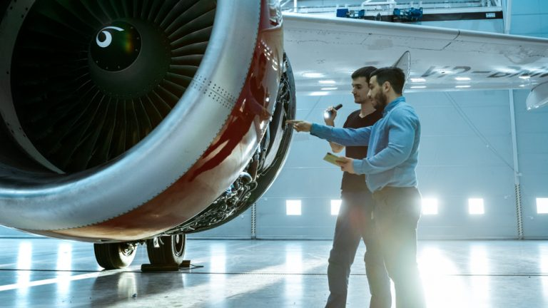 Aircraft Maintenance Engineer Shows Technical Data on Tablet Computer to Airplane Technician, They Diagnose Jet Engine Through Open Hatch. They Stand Near Clean Brand New Plane.