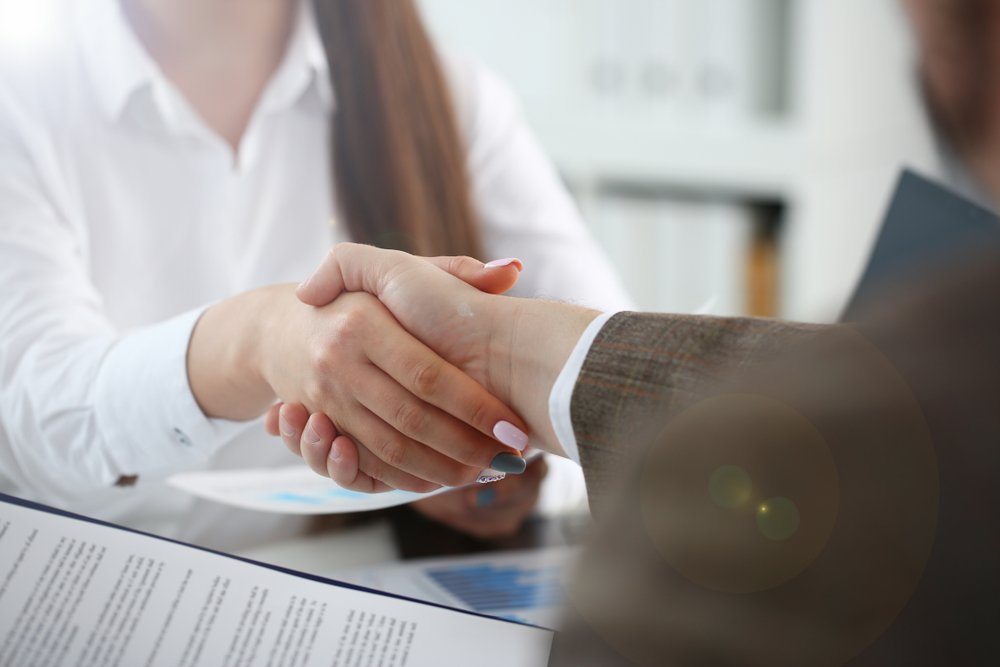 candidate and employer shaking hands at an interview