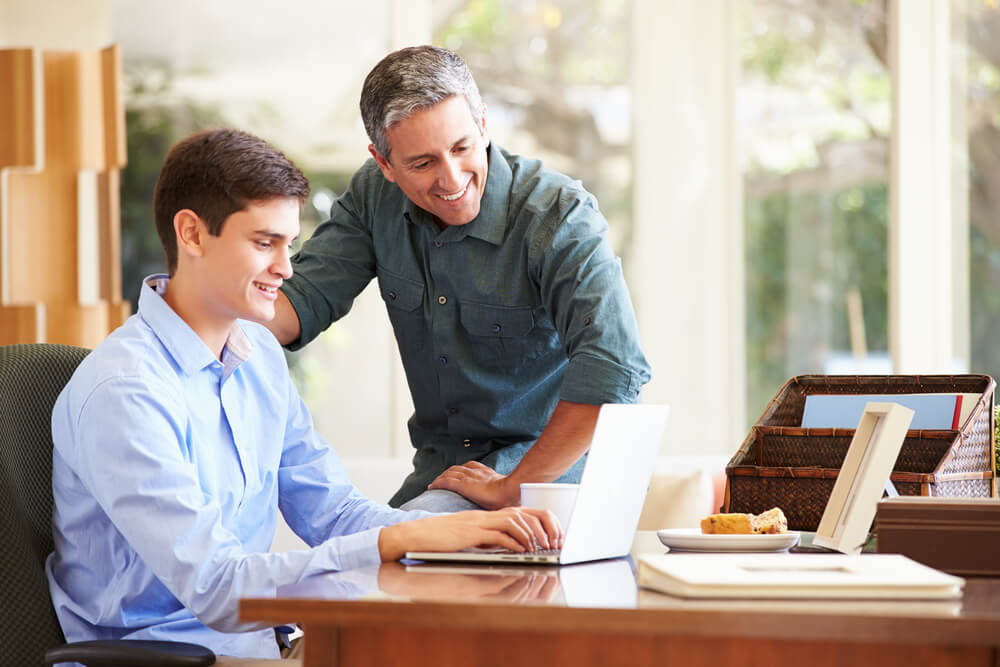 parent and son looking at a laptop together Top Tips for Parents