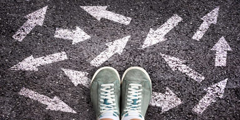 shoes and arrows pointing in different directions on asphalt ground, choice concept