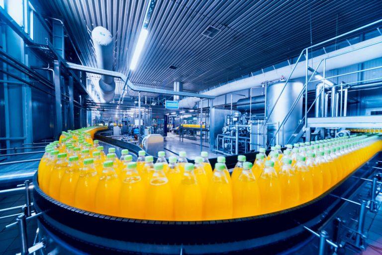Bottles with orange liquid on production line