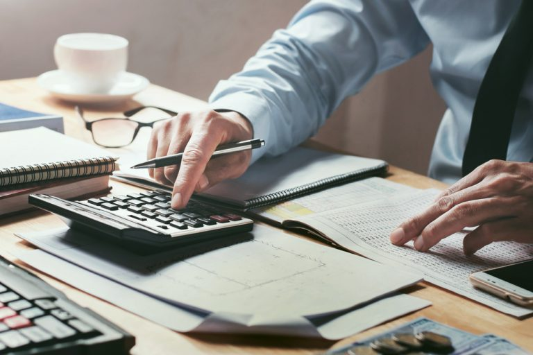 businessman working on desk office with using a calculator to calculate the numbers, finance accounting concept