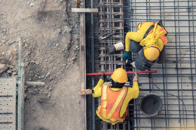 Orange construction workers railway track