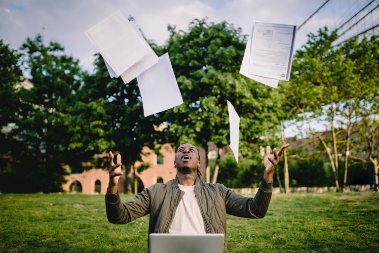 man throwing papers in the air