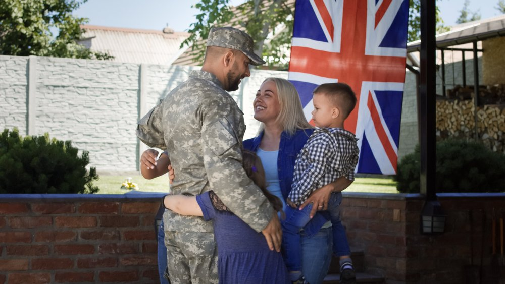 Excited woman with children welcoming serviceman back at home embracing and laughing happily against British flag