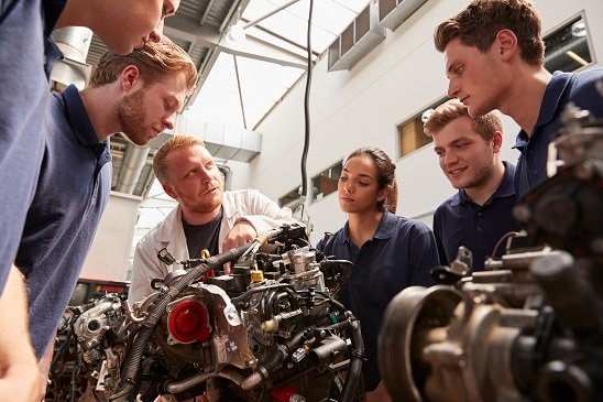 Mechanic showing engines to apprentices, low angle