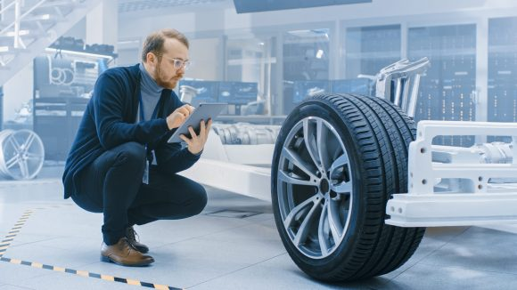Engineer with Glasses and Beard Works on a Tablet Computer Next to an Electric Car Chassis Prototype with Wheels, Batteries and Engine in a High Tech Development Laboratory